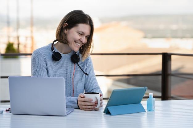 젊은 여자 집 테라스에서 그녀의 태블릿 화상 통화