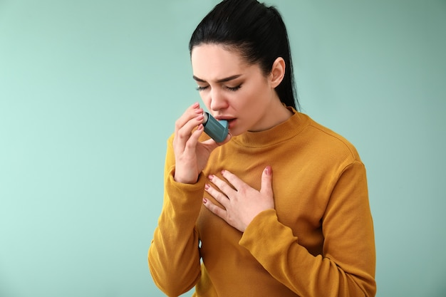 Young woman having asthma attack on color background