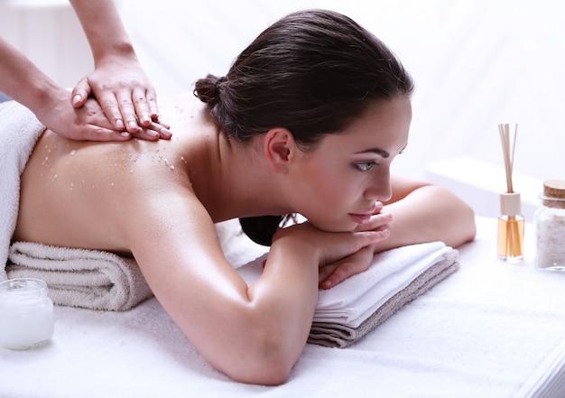 Молодая женщина, имеющая массаж спины и плеч