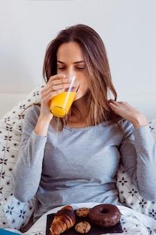 Giovane donna facendo colazione a letto