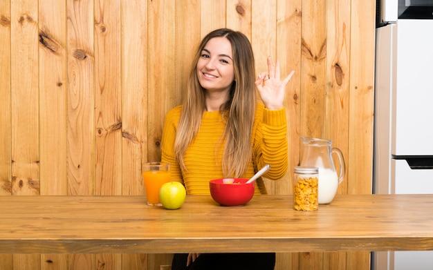 指でokのサインを示す台所で朝食を持つ若い女性