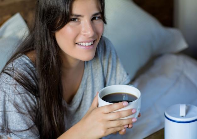ベッドで朝食を持っている若い女性