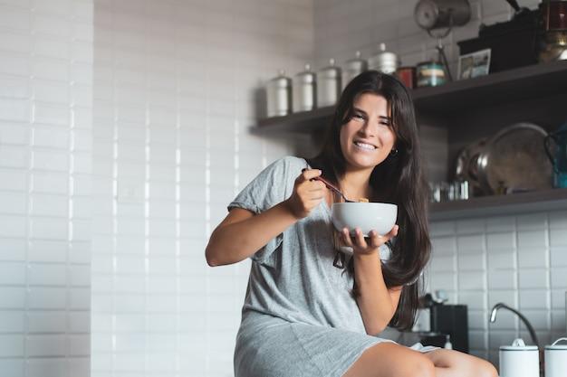 キッチンで朝食を持っている若い女性