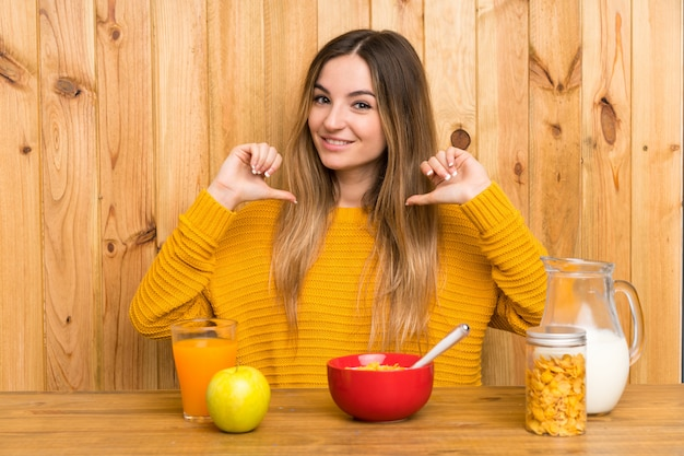 Young woman having breakfast in a kitchen proud and self-satisfied