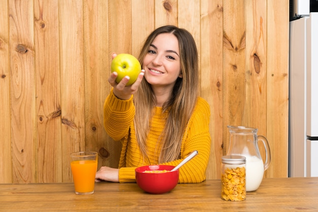 Young woman having breakfast in a kitchen with an apple