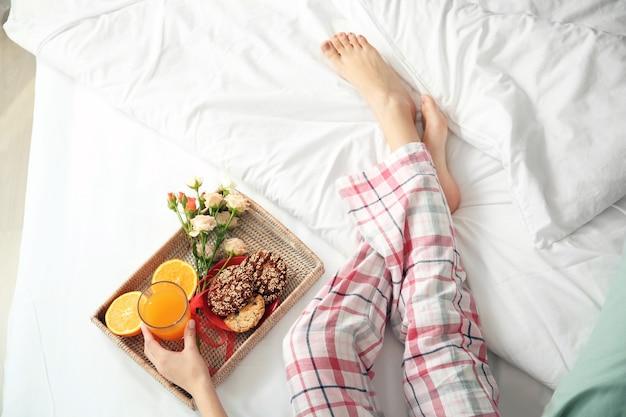 ベッドで朝食をとる若い女性