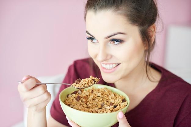 Giovane donna che mangia cereali con latte per colazione