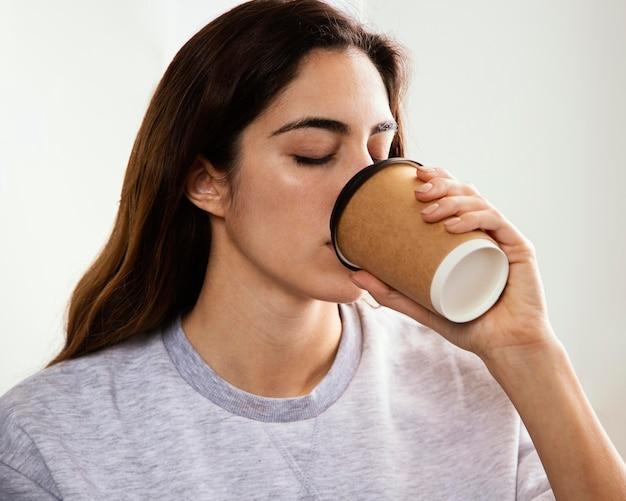 Giovane donna che mangia caffè a casa