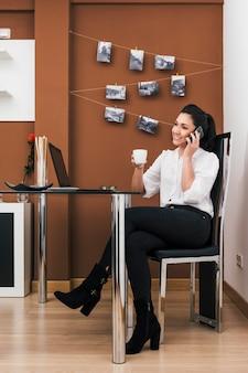 Молодая женщина, имеющая кофе во время разговора по телефону в ее временном домашнем офисе