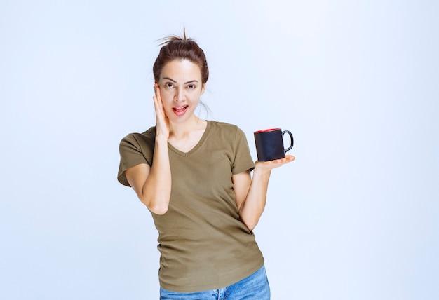 Giovane donna che beve una tazza e si gode il gusto