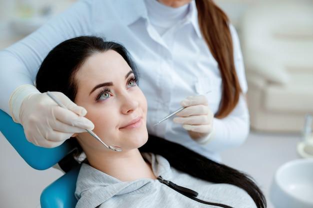 Молодая женщина, имеющая стоматологическое лечение в офисе стоматолога