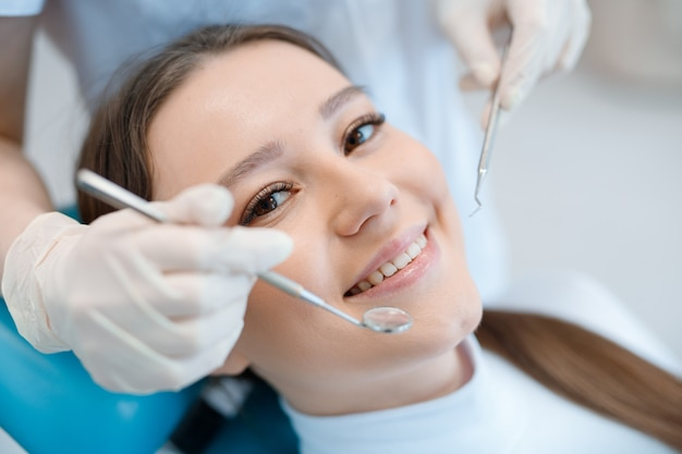 Young woman having dental treatment at dentists office