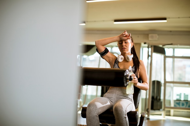 Young woman having exercises on leg extension and leg curl machine in the gym