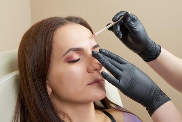 Young woman having eyebrow correction procedure in beauty salon