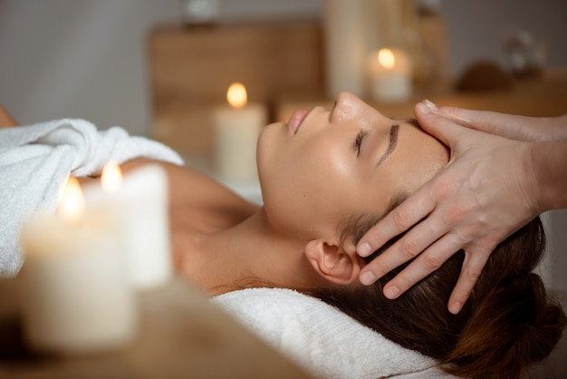 Young woman having face massage relaxing in spa salon.