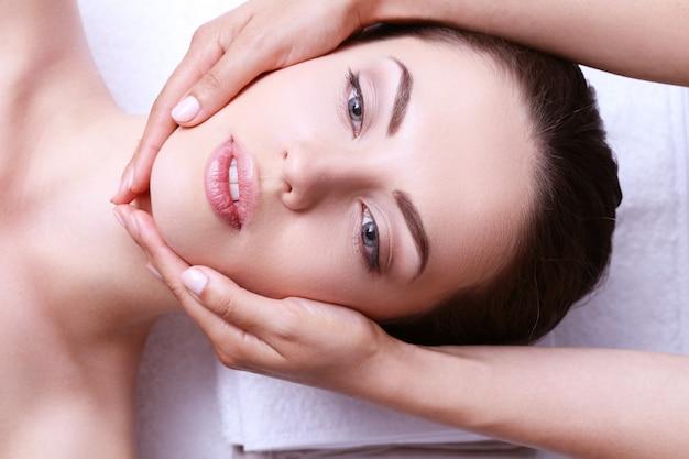 Giovane donna con massaggio viso