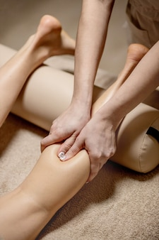 Young woman having feet massage in beauty salon, close up view.
