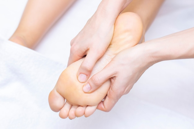 Young woman having feet massage in beauty salon, close up view