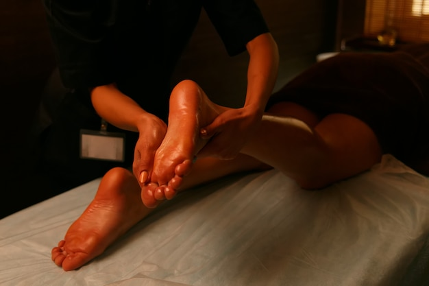 Young woman having feet massage in beauty salon