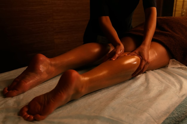 Young woman having feet massage in beauty salon