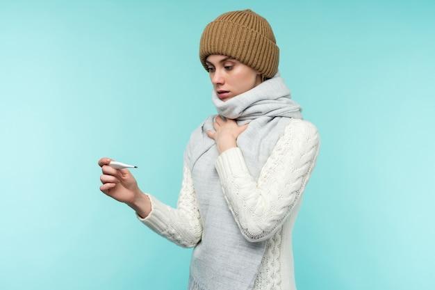 Молодая женщина, имеющая дымоход, принимая термометр на синем фоне. красивая дама больна высокой температурой и болью в горле, изолированный крупный план. концепция простуды, гриппа.