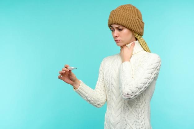 Молодая женщина, имеющая дымоход, принимая термометр на синем фоне. красивая дама заболела высокой температурой и болит горло