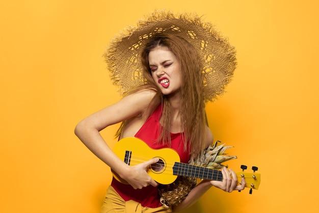 Молодая женщина весело и смеется, вечеринка в купальниках, желтый фон играет на гитаре