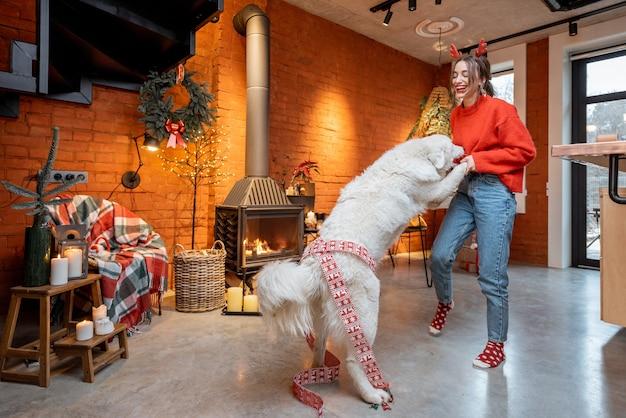 家の暖炉のそばで幸せな新年の休暇中に彼女のかわいい白い犬と一緒に踊るのを楽しんでいる若い女性