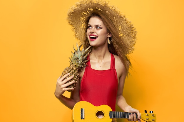 Young woman having fun and laughing, a swimsuit party, a yellow plays the guitar