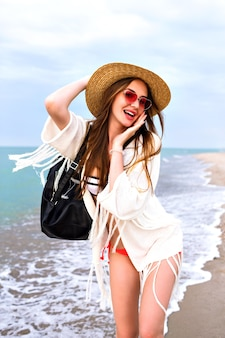 Young woman having fun in lonely beach, enjoy summer vacation and relax, boho outfit, straw hat and bikini