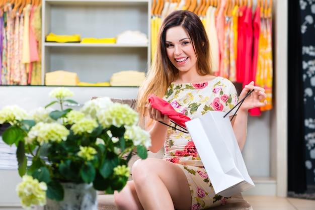 패션 부티크 또는 상점에서 쇼핑하고 의류를 보여주는 동안 재미 젊은 여자