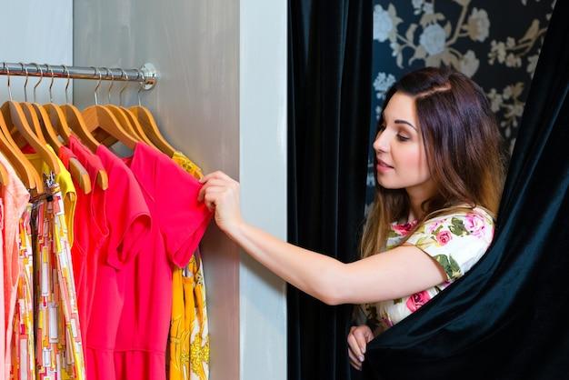 패션 부티크 또는 상점, 랙, 옷, 피팅 오두막에 서서 의류를 테스트하는 동안 재미 젊은 여자