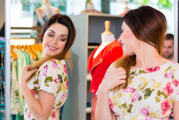 패션 부티크 또는 상점에서 쇼핑하는 동안 재미 젊은 여자