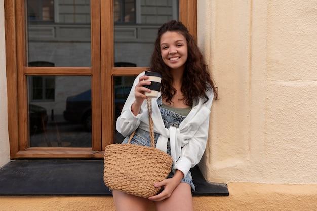 一杯のコーヒーを保持しながら楽しんでいる若い女性