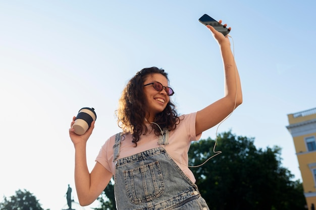 Giovane donna che si diverte mentre tiene in mano una tazza di caffè