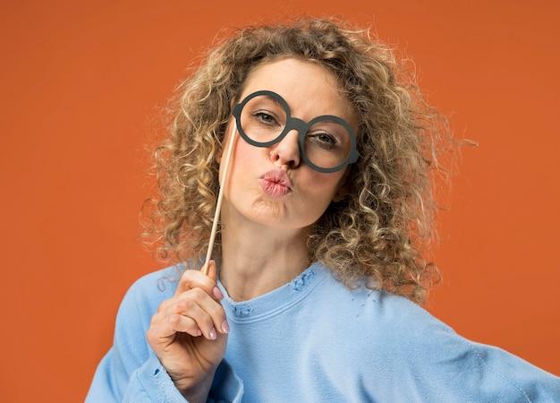 偽のメガネを楽しんでいる若い女性