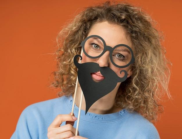 偽の口ひげを楽しんでいる若い女性