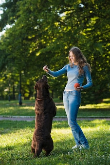 Young woman having fun with her dog in garden