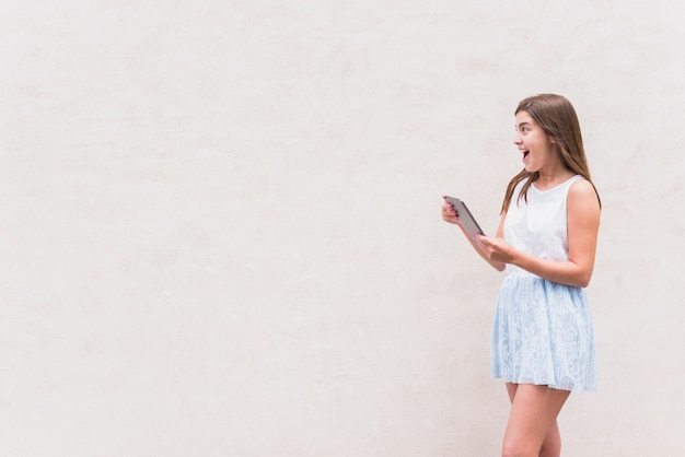 Young woman having fun with tablet on white background