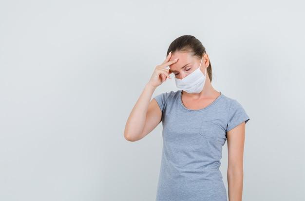 Молодая женщина с головной болью в серой футболке, маске и усталым взглядом, вид спереди.