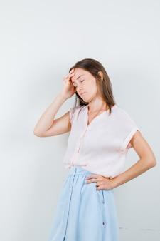 Tシャツ、スカート、疲れているように見える、正面図で頭痛を持っている若い女性。
