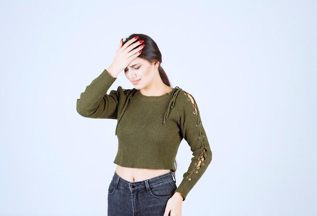 白い背景に頭痛を持つ若い女性。