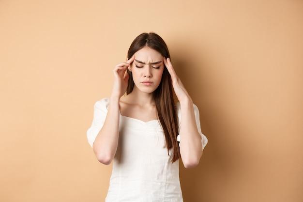 Молодая женщина с головной болью, прикосновением к головным вискам с закрытыми глазами и напряженным лицом, стоя с болезненной мигренью на бежевом фоне.