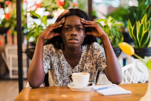 カフェでノートパソコンで作業中に頭痛を抱えている若い女性