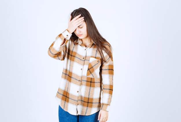Young woman having headache on white wall.