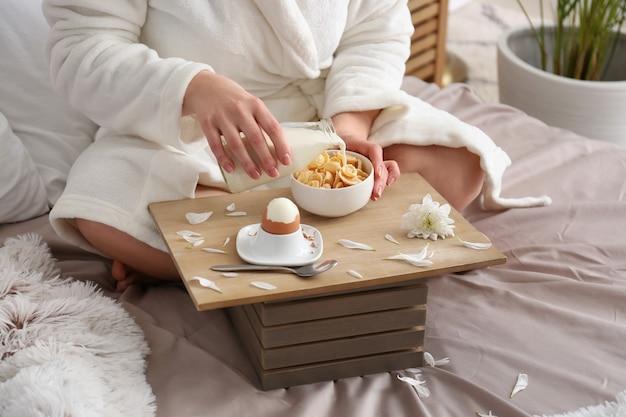 ベッドで健康的な朝食を食べる若い女性