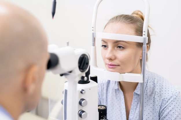 Young woman having her eyesight checked by special optometric equipment in clinics or hospital