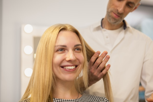Young woman having her hair styled by hairdresser