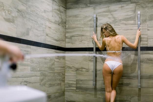 Молодая женщина, имеющие массаж высокого давления с душем шарко. водоподготовка, гидромассаж в современном спа