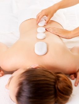 Giovane donna con massaggio con pietre calde nel salone della stazione termale. concetto di trattamento di bellezza.